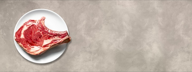 Costela de carne crua e placa isolada sobre fundo claro de concreto. vista do topo. banner horizontal
