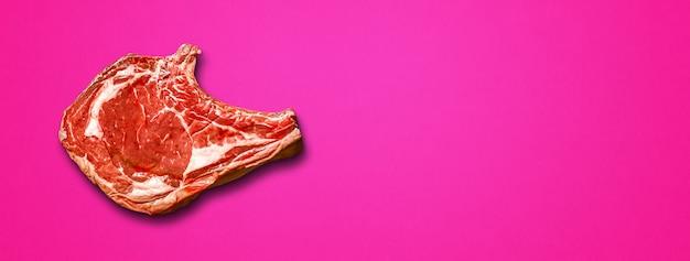 Costela de carne crua isolada em fundo rosa. vista do topo. banner horizontal