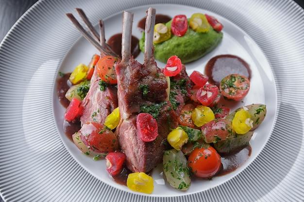 Costela de cordeiro com legumes em um prato branco