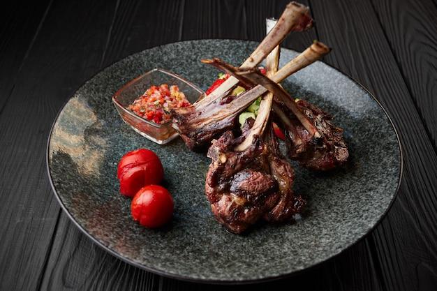 Costela de cordeiro em um prato escuro com tomate e molho