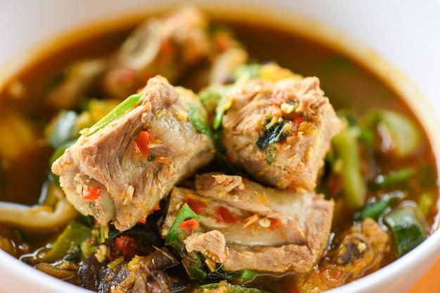 Costela de porco com caril sopa picante / osso de porco com tigela de sopa quente e azeda com legumes tom yum ervas tailandesas comida asiática