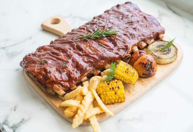Costela grelhada de porco com molho de churrasco e batatas fritas vegetais e frech na tábua de madeira
