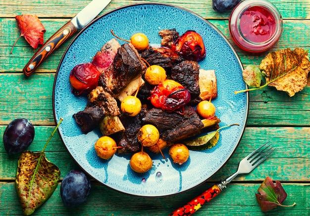 Costelas de carne assadas em ameixas e peras. costelas de carne grelhadas em molho de frutas. comida de outono