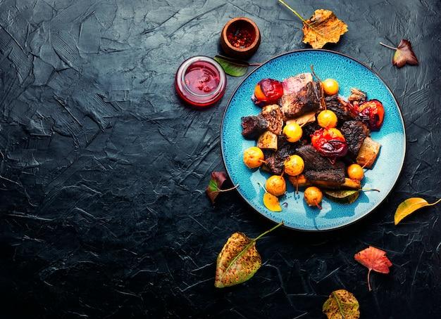 Costelas de carne assadas em ameixas e peras. costelas de carne grelhadas em molho de frutas no prato. copie o espaço