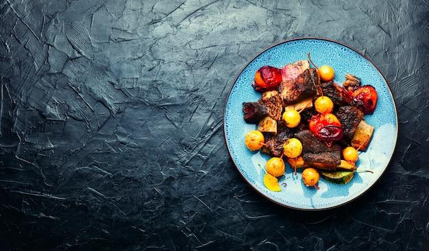 Costelas de carne assadas em ameixas e peras. costelas de carne grelhadas em molho de frutas.