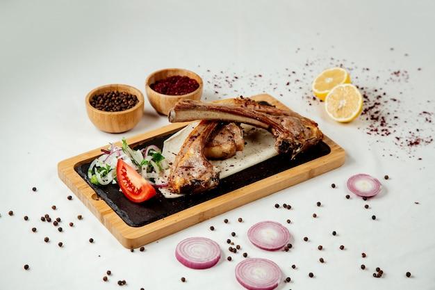 Costelas de carne com cebola em uma placa de madeira