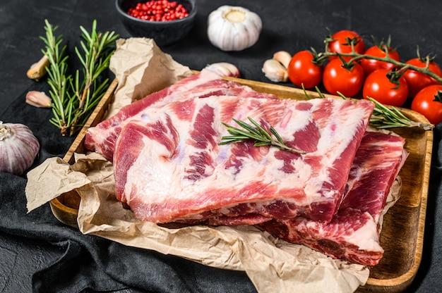 Costelas de carne de porco cru com ingredientes para cozinhar alecrim e alho em uma tigela de madeira. vista do topo