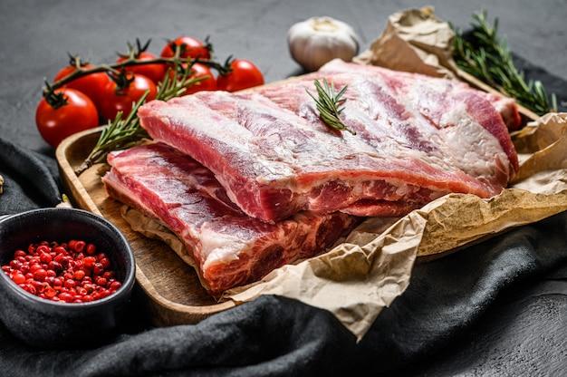 Costelas de carne de porco crua com ingredientes para cozinhar alecrim e alho em uma tigela de madeira.