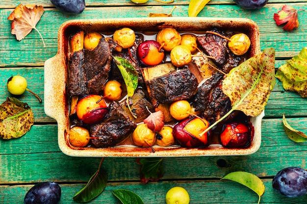Costelas de carne grelhadas com ameixas e peras na assadeira. costelas de carne fritas em molho de frutas. vista superior