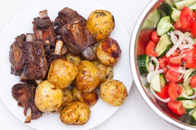 Costelas de churrasco com batatas e salada com tomates e pepinos
