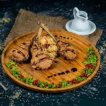 Costelas de cordeiro assadas com arroz em um prato redondo de madeira em um fundo escuro texturizado