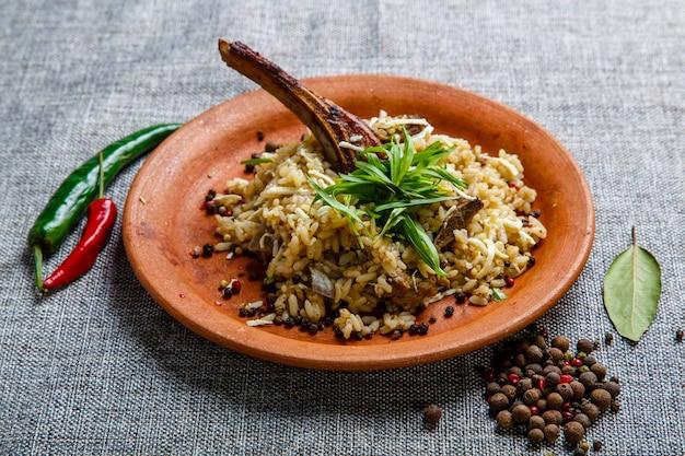Costelas de cordeiro com arroz em um prato de barro. tela cinza texturizada. ao lado do prato estão vagens de pimenta e ervilhas, folha de louro. cozinha georgiana.