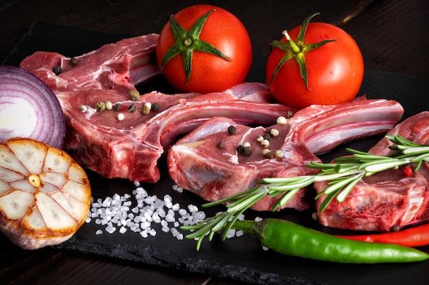 Costelas de cordeiro de carneiro de carne crua com ervas em pedra preta com especiarias e legumes frescos