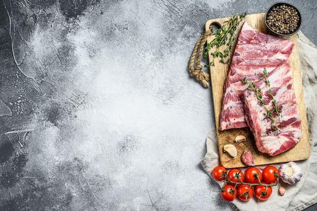 Costelas de porco cru fresco com alecrim, pimenta e alho. fazenda de carne orgânica. fundo cinza. vista do topo. espaço para texto