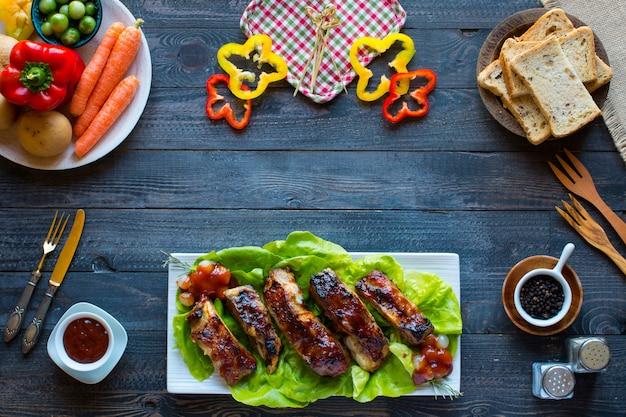 Costelas de porco de churrasco grelhado com legumes em uma mesa de madeira