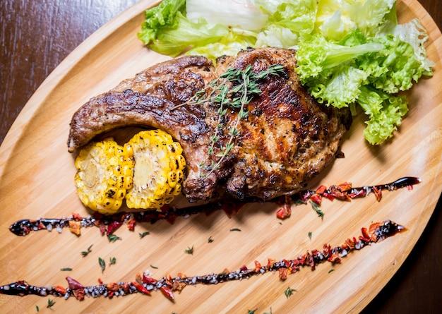 Costelas de porco grelhadas com milho e salada em uma placa de madeira. comida americana com especiarias. restaurante.
