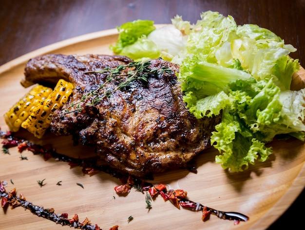 Costelas de porco grelhadas com milho e salada em uma placa de madeira.