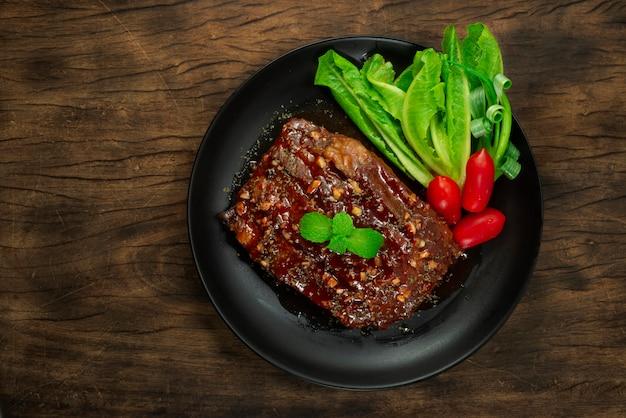 Costelas de porco para churrasco com molho servido com legumes e tomate
