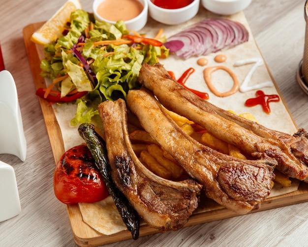Costelas fritas batatas fritas tomate salada verde vista lateral