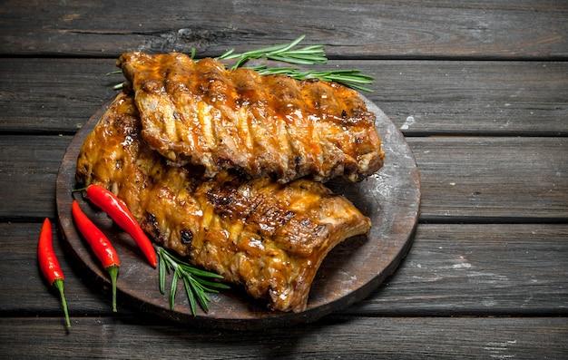 Costelas grelhadas com alecrim e pimenta malagueta em uma mesa rústica.