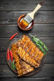 Costelas grelhadas com alecrim e pimenta malagueta na mesa de madeira.