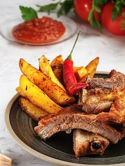 Costelas grelhadas com batatas fritas e legumes. lantejoulas de gordura na carne. profundidade superficial de campo.