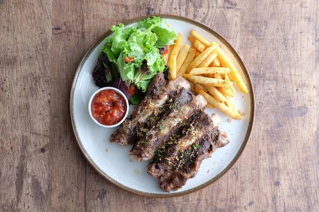 Costelas grelhadas com batatas fritas e molho de pimenta