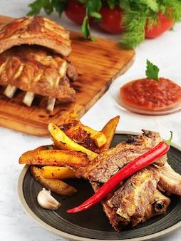 Costelas grelhadas com batatas idaho e legumes no prato. lantejoulas de gordura na carne. profundidade superficial de campo.