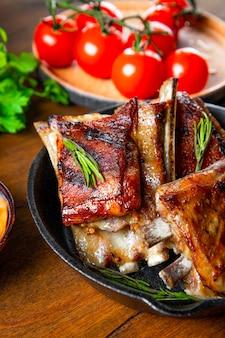 Costelas grelhadas em molho barbecue com tomate fecham foto vertical. foto de alta qualidade