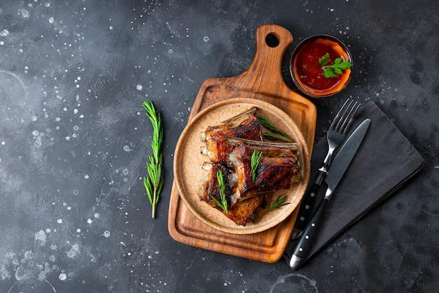 Costelas grelhadas em molho barbecue no prato e vista superior do plano de fundo cinza, copyspace. foto de alta qualidade