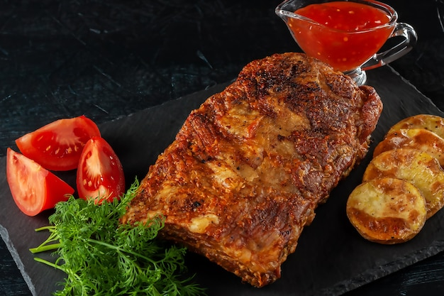Costelas picantes grelhadas servidas com molho de pimenta quente e tomates frescos