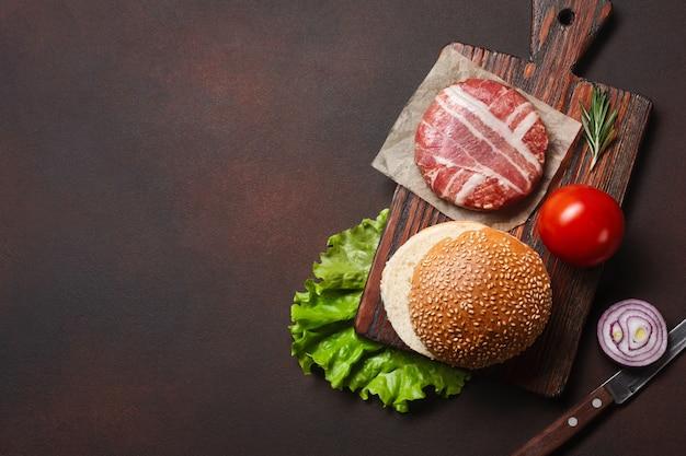 Costeleta crua de ingredientes de hambúrguer, tomate, alface, pão, queijo, pepino e cebola no fundo enferrujado