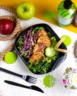 Costeleta de brócolis e batata superior servida com salada de repolho na caixa de entrega na mesa de madeira