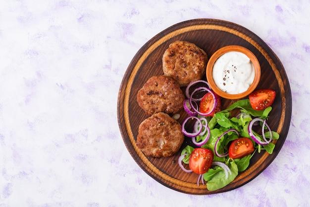 Costeleta de carne apetitosa e salada de tomate com rúcula