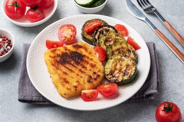 Costeleta de carneiro de frango e abobrinha cozida na grelha. tomates frescos em um prato. pronto jantar delicioso almoço.