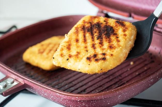Costeleta de carneiro fritada na bandeja da grade. dois pedaços de cordon bleu com presunto e queijo em uma panela.