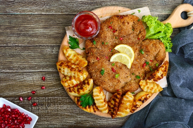 Costeleta de carneiro grande com as batatas douradas cozidas em uma placa de corte de madeira. wiener schnitzel. vista do topo.