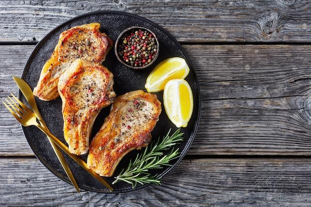 Costeleta de costela de porco frita com rodelas de limão, alecrim, pimenta em grão e garfo e faca dourados em uma travessa preta