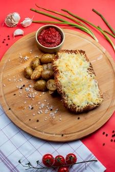 Costeleta de frango coberta com queijo derretido e batatas laterais
