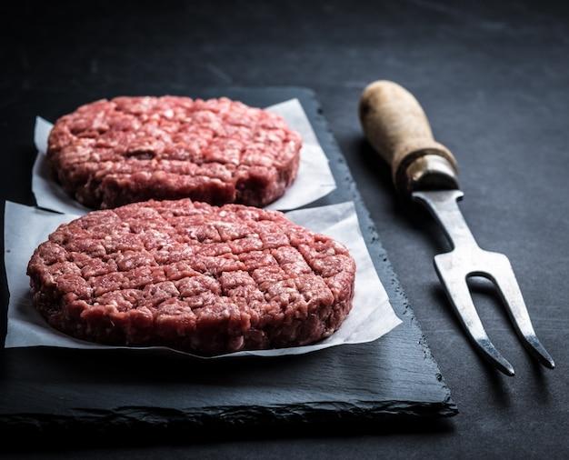 Costeleta de hambúrguer cru na ardósia de cozinha