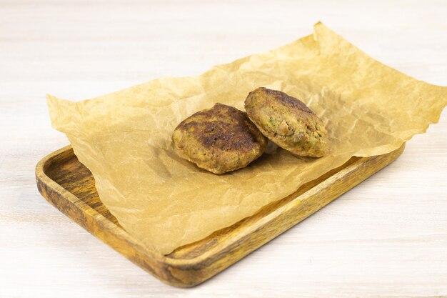 Costeleta de hambúrguer de carne bovina caseira na bandeja de madeira, papel manteiga na mesa branca. conceito de dieta baixa em carboidratos. fechar-se. foco seletivo. copie o espaço