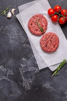Costeleta de hambúrguer de carne crua fresca com ervas e especiarias no quadro de pedra preta, vista superior