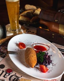 Costeleta de kiev de frango servida com salada de repolho, verduras, molho e fatias de tomate