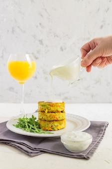 Costeleta de legumes saborosa de cenoura, abobrinha, milho e ervilha com molho branco e copo de suco de laranja