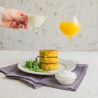 Costeleta de legumes saborosa de cenoura, abobrinha, milho e ervilha com molho branco e copo de suco de laranja.