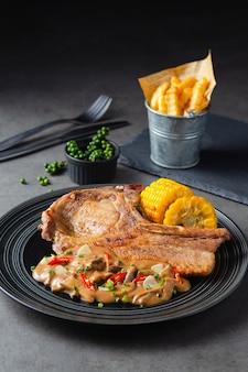 Costeleta de porco com molho de cogumelos e batatas fritas colar sobre um fundo preto.