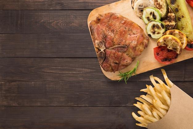 Costeleta de porco e batatas fritas grelhadas no fundo de madeira. copyspace para o seu texto