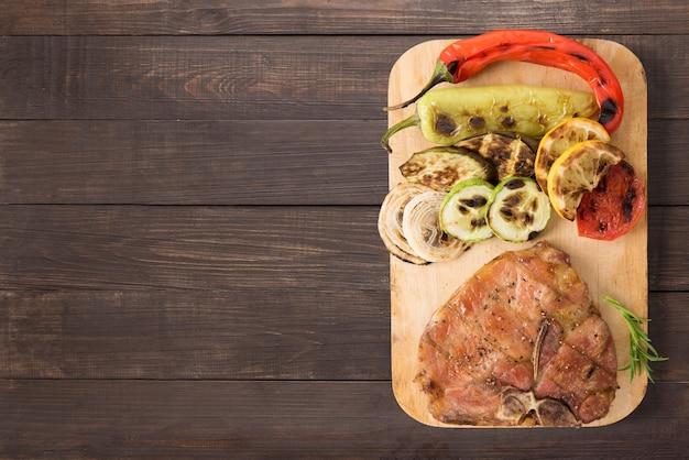 Costeleta de porco e legumes grelhados no fundo de madeira. copyspace para o seu texto