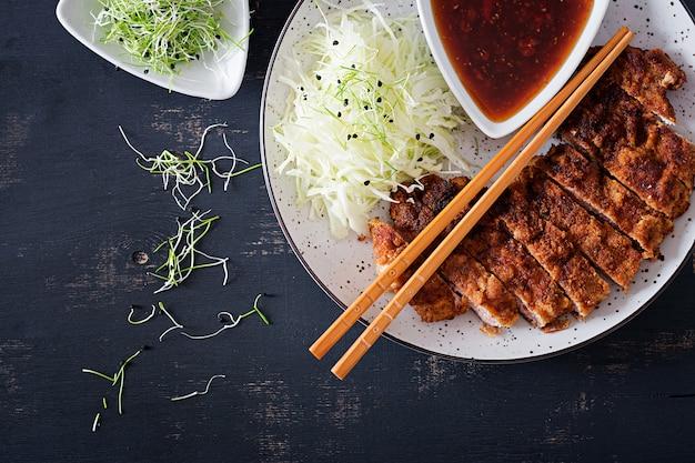 Costeleta de porco frita com repolho e molho tonkatsu.