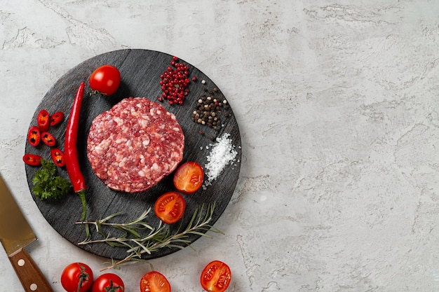 Costeleta fresca e crua feita em casa com especiarias e tomates na mesa, close-up